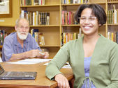 Two smiling , European old man and African girl, in librar — Stock Photo