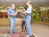 Multiracial group of friendly chatting in library — Stok fotoğraf