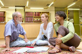 Professor with students sit on carpet — Stock Photo