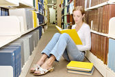 Slim girl sits on floor in library and reads book — Stock Photo