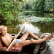 Boy lying in motor boats on river — Stock Photo