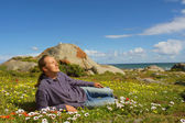 Young man relaxes lying on flower field — Stock Photo