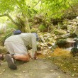 Old man drinks from little mountain river — Stock Photo #20990497