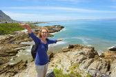 笑的女人站在陡峭的岩石上 — 图库照片