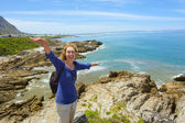 Laughing woman stands on steep rock — Stock Photo