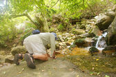 Old man drinks from little mountain river — Stock Photo