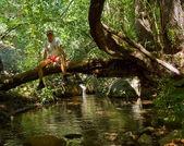 男人坐在倒下的树上 — 图库照片