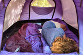 Woman sleeping inside blue tent — Stock Photo