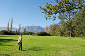 Woman in park looks at mountains — Stok fotoğraf