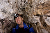 Happy smiling hiker in a cave — Stock Photo