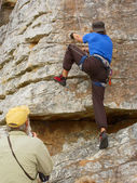 Old coach looks at rock climber — Stock Photo