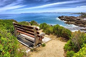 Bench on rocks under dramatic skies — Stok fotoğraf