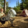 Smiling old hiker in the camp in morning forest — Stock Photo