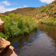 Little river winds between red mountains — Stock Photo