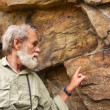 Постер, плакат: Old man points at the ancient bushman paintings