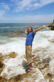 Happy man stands in foamy wave — Stock Photo