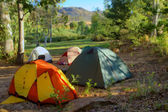 Hiker's camp in morning forest in mountains — Stock Photo