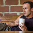 Young man holds a coffee cup — Stock Photo