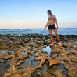 Man stands on rocky beach — Stock Photo