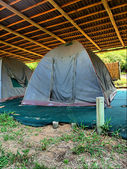 Old camping tent under roof — Stock Photo