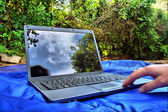 Hand touches the laptop reflecting skies — Stock Photo