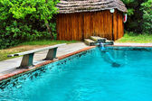 House and bench next to pool — Stock Photo
