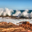������, ������: Row of wave splashes on red rock beach