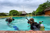 Two divers in training pool under storm skies — Stock Photo