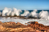 Row of wave splashes on red rock beach — Stock Photo