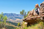 Blonde girl sits on rock and looks at mountains — Foto Stock