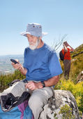 Old backpacker sending sms sitting on rock — Stock Photo