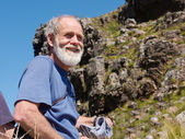Happy old man in mountains — Stock Photo