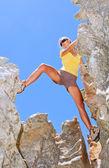 Female rock climber steps between rocks — Stock Photo