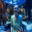 Happy woman looks at clown fish through glass — Stock Photo