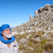 Old man in bedouin clothes looks at mountains - Foto Stock