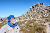 Old man in bedouin clothes looks at mountains — Stock Photo