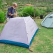 Senior hiker assembles tents on camping site - Stock Photo