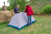 Two hikers assemble tents on camping site — Stock Photo