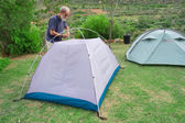 Senior hiker assembles tents on camping site — Stock Photo