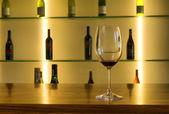 Sklenice na víno proti pole lahví — Stock fotografie