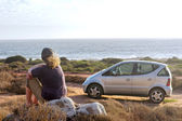 Woman dreams while sitting on beach next to her car — Stok fotoğraf