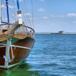 Wooden yacht enters sea port — Stock Photo #25293127