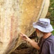 Постер, плакат: Old man points at bushman rock paintings