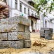 Stock Photo: Piles of bricks against renovated building