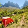 Red camping tent next to trail in mountains - Stock Photo