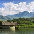 Lake house against mountains and Cathkin peak - Stock Photo