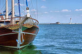Wooden yacht enters sea port — Stock Photo