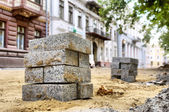 Piles of bricks against renovated building — Stock Photo