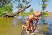 Happy wet boy climbs on rock in lake — Stock Photo
