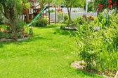 Children playground in sunny garden — Stock Photo